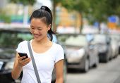 image of parking lot  - woman use her cellphone walking at parking lot - JPG