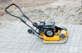 picture of vibration plate  - Small yellow compactor standing on new gray  pavement - JPG