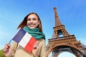 stock photo of fall day  - Happy woman travel in Paris with eiffel tower and beautiful blue sky and holding France French flag caucasian beauty - JPG