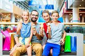 pic of mall  - Family eating ice cream in shopping mall with bags - JPG