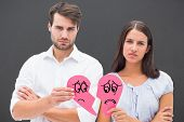 picture of two hearts  - Upset couple holding two halves of broken heart against grey - JPG