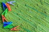foto of pegging  - colorful plastic clothes pegs on green fabric - JPG