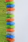 pic of pegging  - colorful plastic clothes pegs on green fabric - JPG