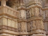 stock photo of kama  - Sculptures of loving couples illustrating the Kama Sutra on walls of Varaha Temple Khajuraho in India Asia - JPG