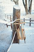 picture of sled  - Vintage wood sled leaning on bridge in snowy mountain scene - JPG