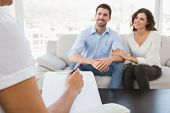 stock photo of therapist  - Reconciled couple smiling and talking with their therapist in the office - JPG