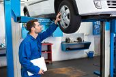 picture of garage  - Mechanic looking at car tires at the repair garage - JPG