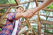 stock photo of angle  - Low angle view of confident architect greeting colleague at construction site - JPG