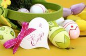 pic of gift basket  - Happy Easter green and yellow felt basket of of pink white and green easter eggs on rustic vintage yellow wood table with heart shape greeting card closeup - JPG