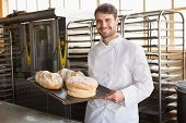 pic of trays  - Happy baker showing tray with bread at the bakery - JPG