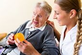 picture of geriatric  - Nurse giving physical therapy with massage ball to senior woman in wheelchair - JPG