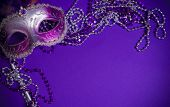stock photo of masquerade mask  - A purple mardi gras mask on a purple background with beads - JPG