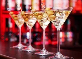 image of shot glasses  - Several glasses of famous cocktail Martini shot at a bar with shallow depth of field - JPG
