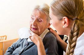 stock photo of nursing  - Nurse wiping mouth of elderly senior woman in nursing home - JPG
