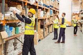stock photo of packages  - Warehouse worker taking package in the shelf in a large warehouse in a large warehouse - JPG