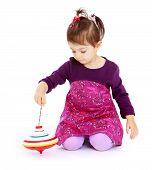 picture of dreidel  - Very little girl sitting on the floor and spinning the dreidel - JPG