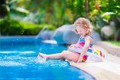 stock photo of floating  - Kids in swimming pool - JPG