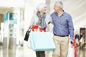 stock photo of mall  - Happy Senior Couple Carrying Bags In Shopping Mall - JPG