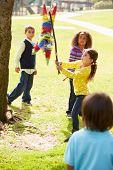 picture of pinata  - Children Hitting Pinata At Birthday Party - JPG