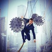 foto of unsafe  - Businessman hindered by balls balanced on rope - JPG
