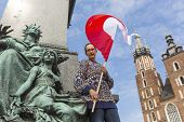 picture of polonia  - Young woman with the flag of the Republic of Poland on the main square of Krakow - JPG