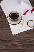 stock photo of private investigator  - Coffee cup paper sheets and detective hat on old Wooden table - JPG