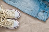 picture of paper craft  - Old torn blue jeans and shoes on craft paper - JPG