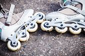 stock photo of inline skating  - Active fun leisure in spring summer outdoor activities concept. Closeup roller skates on asphalt. ** Note: Soft Focus at 100%, best at smaller sizes - JPG