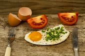 pic of human egg  - fried egg topped with onions and tomatoes on wooden background - JPG