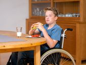 stock photo of baps  - disabled boy in wheelchair is eating in the living room  - JPG