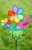 stock photo of grass bird  - Colorful double pinwheel with bird on a green grass - JPG