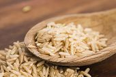 image of spoon  - Spoon of brown rice on a wooden table - JPG