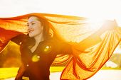 picture of flutter  - Smiling happy woman with long brown fluttering scarf on sunset - JPG