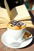 stock photo of treble clef  - Cups of cappuccino with treble clef on foam  and book on table in cafe - JPG