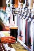 stock photo of draft  - Bartender pouring draft beer in the bar. ** Note: Shallow depth of field - JPG
