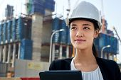 stock photo of hard_hat  - professional asian chinese business woman supervising construction site with hard hat protection at work - JPG