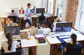 stock photo of fifties  - Wide Angle View Of Busy Design Office With Workers At Desks - JPG