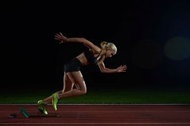 foto of sprinters  - woman  sprinter leaving starting blocks on the athletic  track - JPG