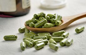 stock photo of laxatives  - Moringa capsule pills in the wood spoon - JPG
