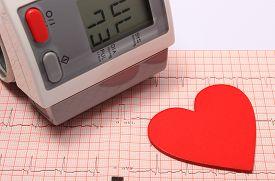 stock photo of ekg  - Instrument for measuring blood pressure and red heart shape on electrocardiogram graph ekg heart rhythm medicine concept - JPG