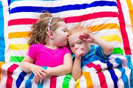 picture of boys night out  - Two kids sleeping in bed under colorful blanket - JPG