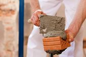 image of grout  - bricklayer laying bricks to make a wall - JPG
