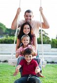 stock photo of family fun  - Family having fun on a swing - JPG