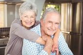 Portrait of cheerful senior couple embracing in kitchen at home poster
