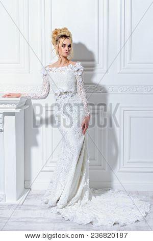 poster of Full length portrait of a magnificent young woman in elegant long white dress. Luxurious apartments.