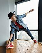 Teenager Guy In Denim Jacket And Baseball Cap, Jeans And Sneakers Dancing At Window Of Dance Studio. poster