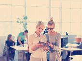 Business Women Using Digital Tablet in Busy Office poster