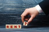 Hand Holds A Cube With The Symbol Of An Exclamation Point To The Word Rent. Renting And Renting A Ho poster