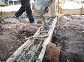 Construction Workers Pouring Wet Concrete To Reinforcement Wooden Framework poster