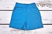 Kids Blue Cotton Pockets Shorts. Baby Boy Casual Textile Shorts On White Wooden Background. Toddler  poster